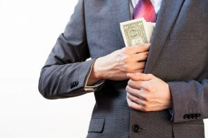 Man stuffing money in jacket pocket